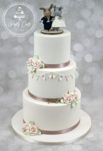 3 Tier Ivory Wedding Cake With Roses And Handpainted Bunting.